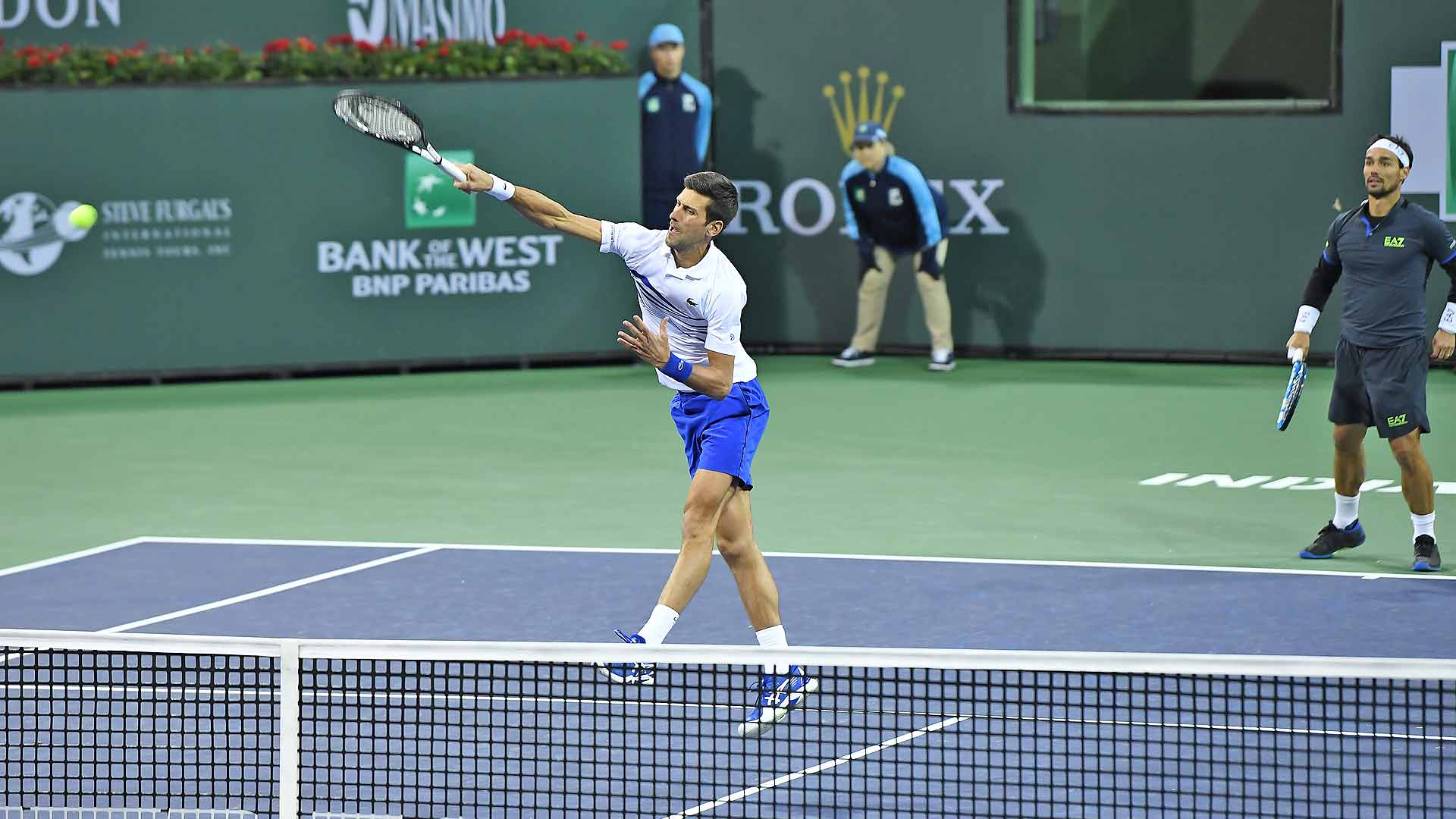 Novak Djokovic hits an overhead as partner Fabio Fognini looks on in the second round of doubles at the 2019 BNP Paribas Open