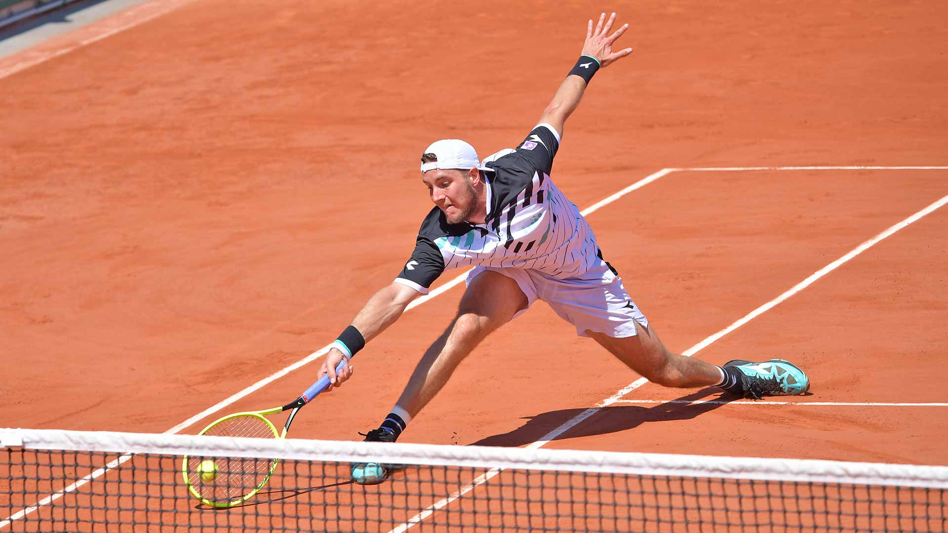 Jan-Lennard Struff stretches for a forehand at Roland Garros